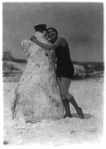 Woman in bathing suit hugging a snowman - 1924